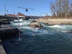 White water slalom gates on a fast river rapids. Fast blue river with water sports facilities for kayak and canoe