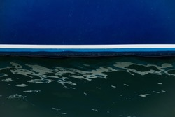 White waterline on the side of the Blue Yacht and highlights on seawater painted blue.