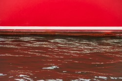White waterline on the side of the red yacht and highlights on seawater painted red.