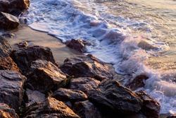 White wave of sea clash the  stones.  sea splash and the rock background.  scenic of beach.  black stone on coast.