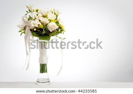 White wedding bouquet in vase on a white background with vignette
