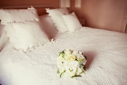 white wedding bouquet on a bed