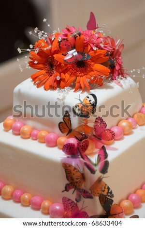 stock photo White wedding cake closeup with red and pink flowers