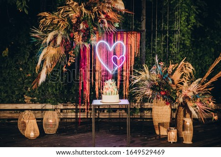 white wedding cake stands on a wooden table against a background of decorations from plants and dried flowers Stock foto ©