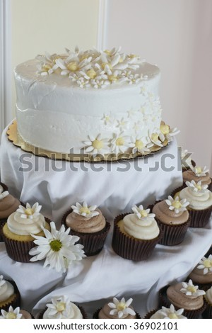 stock photo White wedding cake with cupcakes at reception table