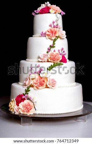 White wedding cake with flowers and leaves on black background white wedding cake with flowers and leaves on black background isolated mightylinksfo
