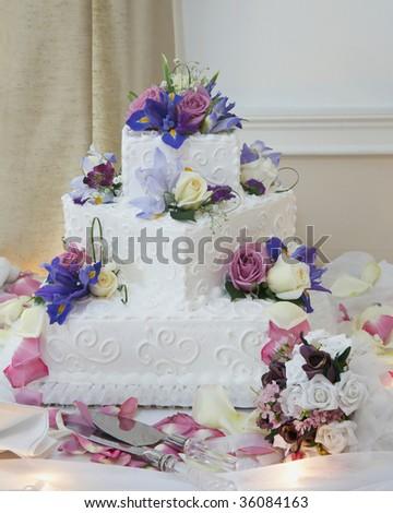 White wedding cake with flowers at reception table