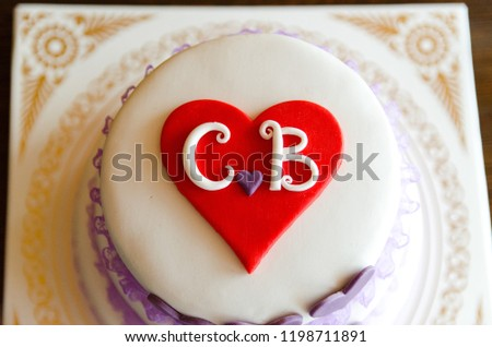 white wedding cake with letters c and b 1198711891
