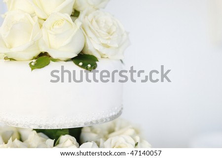 White wedding cake with real roses decorations