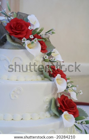stock photo : White wedding cake with red roses on table at reception