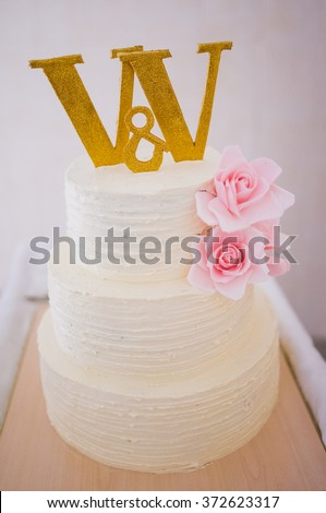 white wedding cake with roses on and letter v v on it 372623317