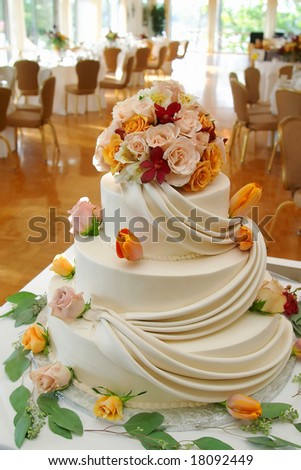 stock photo White wedding cake with roses on reception table