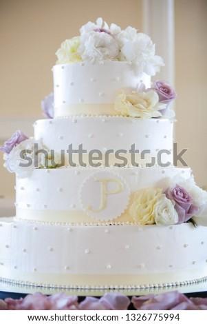 White wedding cake with yellow, white, and purple flowers. wedding cake series