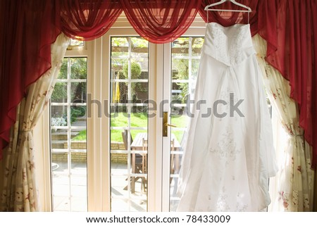 white Wedding dress hanging from a curtain pole