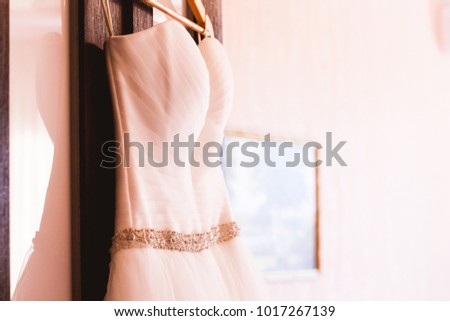 White wedding dress on hanger. Bridal fashion and beauty. Beautiful  elegance cloth, gown for bride. Marriage celebration elegant background. Fabric luxury clothing. #1017267139