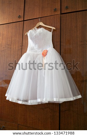 White wedding dress with orange bud on hanger