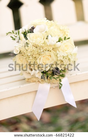 White wedding flowers on white wooden bench