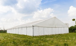 white wedding or entertainment tent in a grass field on a sunny summer's day