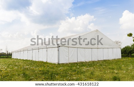 white wedding or entertainment tent in a grass field on a sunny summer's day #431618122