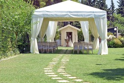 white wedding or entertainment tent with a very small chapel, and a baptism bowl, in a grass field on a sunny summer's day