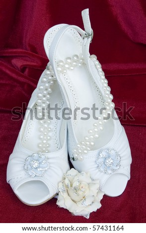 stock photo White wedding shoes with necklace from pearls on red