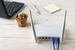 White Wi-Fi wireless router near laptop on a white wooden table. Wlan router with internet cables plugged in on a table in a home or office. Rear view.
