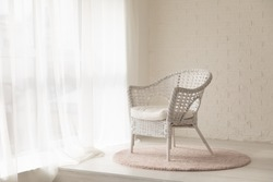 White wicker armchair standing in empty modern room with big windows, curtains and soft carpet rug, elegant and quiet cozy interior in daylight, decorative brick wall, nursery or bedroom