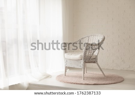 White wicker armchair standing in empty modern room with big windows, curtains and soft carpet rug, elegant and quiet cozy interior in daylight, decorative brick wall, nursery or bedroom 商業照片 ©
