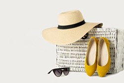 White wicker suitcase, female hat, sunglasses and yellow shoes.