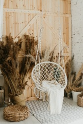 White wicker swing chair, cute interior. White bedroom, cozy house. The interior design of the nursery concept