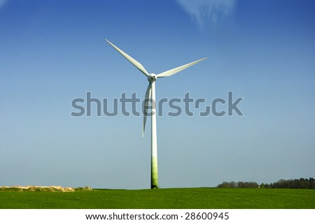 white wind energy station with almost cloudless sky in background