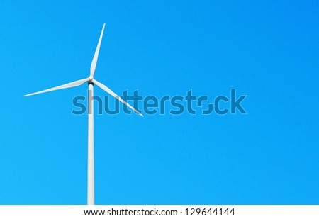 white wind turbine against a vibrant blue sky (copy-space for your design)