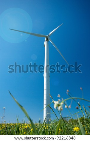White wind turbine electric power generator under blue sky - stock photo