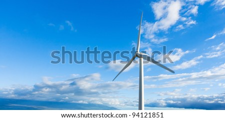 White Wind Turbine Generating Electricity on Blue Sky