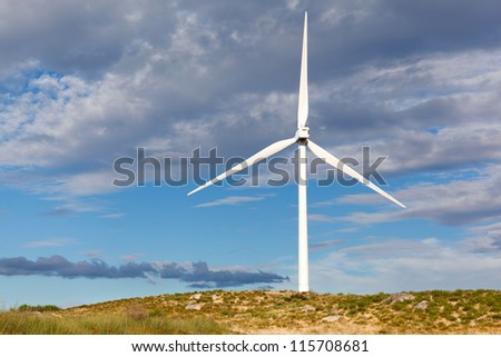 White wind turbine in the top of the mountain generating electricity