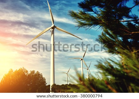 White wind turbine located outside the city, electric generator against beautiful cloudy sky and sunset, alternative energy resources, windmill in field at evening