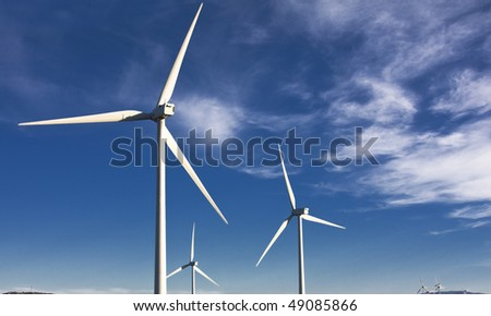 white wind turbines in the top of the mountain