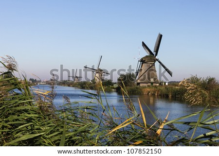 White windmill and house near river in Holland