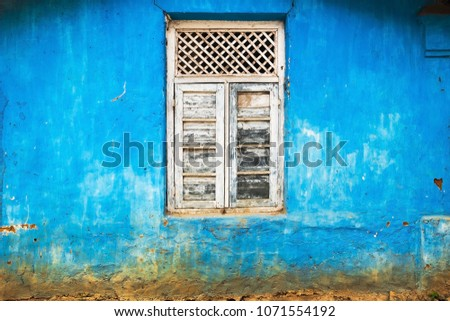 White window on blue old wall. Nobody on photo. #1071554192