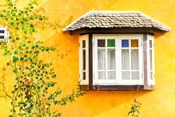 White window on yellow wall