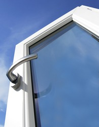 White window with silver handle with blue sky in the background
