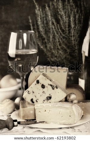 White wine and Various types of cheese on a plate (sepia toned)
