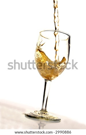 White wine being poured into a glass on white