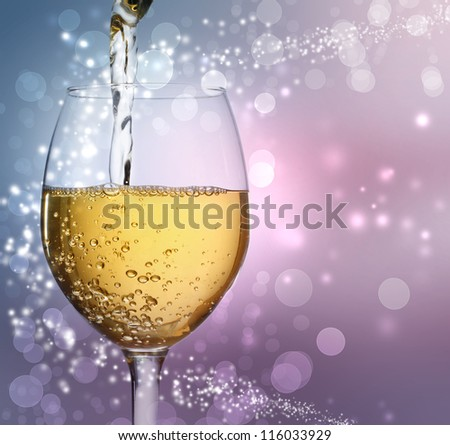 White wine being poured into a wine glass on abstract lights background
