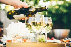 White wine being poured into glass. Concept of celebration, party outdoors.