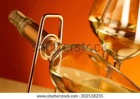 White wine bottle on a metal wine rack and two glasses with white wine