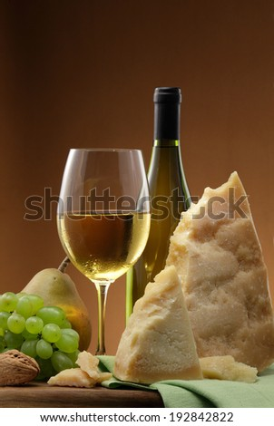 White wine bottle,  white wine glass, white wine grapes and parmegiano cheese still life