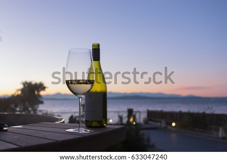 White wine glass and bottle on outside table at sunset