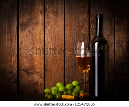 White wine, grapes, corkscrew, and bottle on wood background closeup