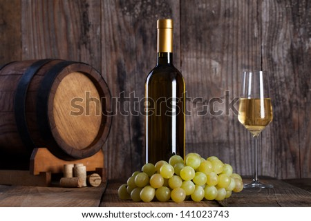 White wine, grapes, old bottle and a barrel